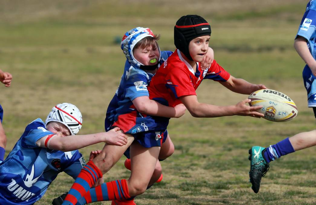 OFFLOADING: Kangaroos under 10s' Harry Rynehart looks for support despite the efforts of Tumut defenders.