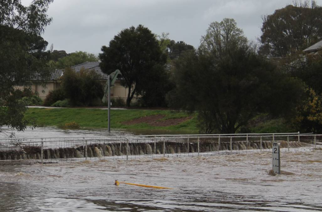 Flooding in Cootamundra in September 2016. Picture shows Thompson Street footbridge about an hour before the weight of the water and debris buckled the handrails. Picture by Jennette Lees